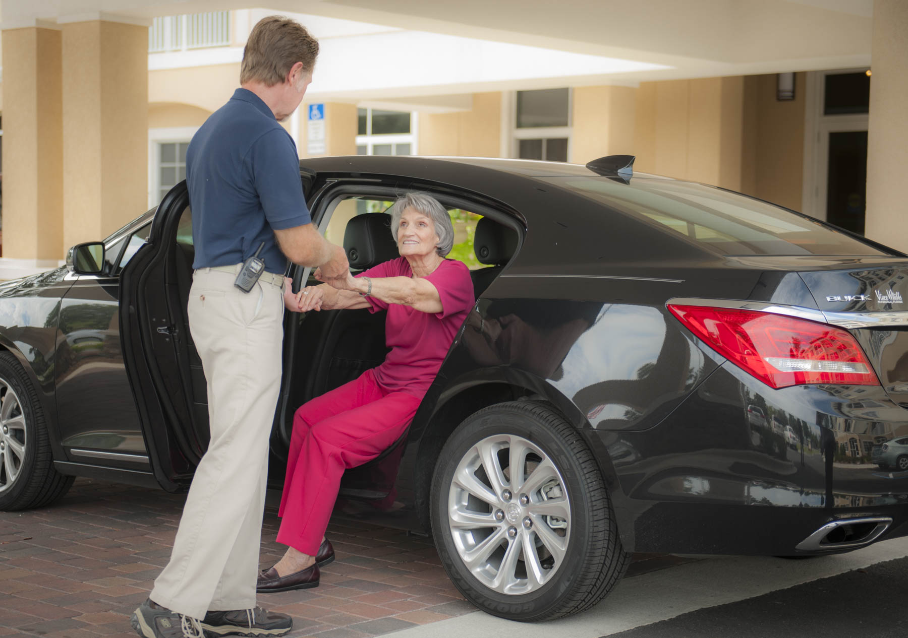 Valet helping a senior woman out of car at assisted living and memory care community