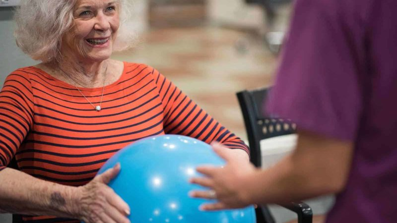 Senior woman holding rubber ball with assisted living nurse