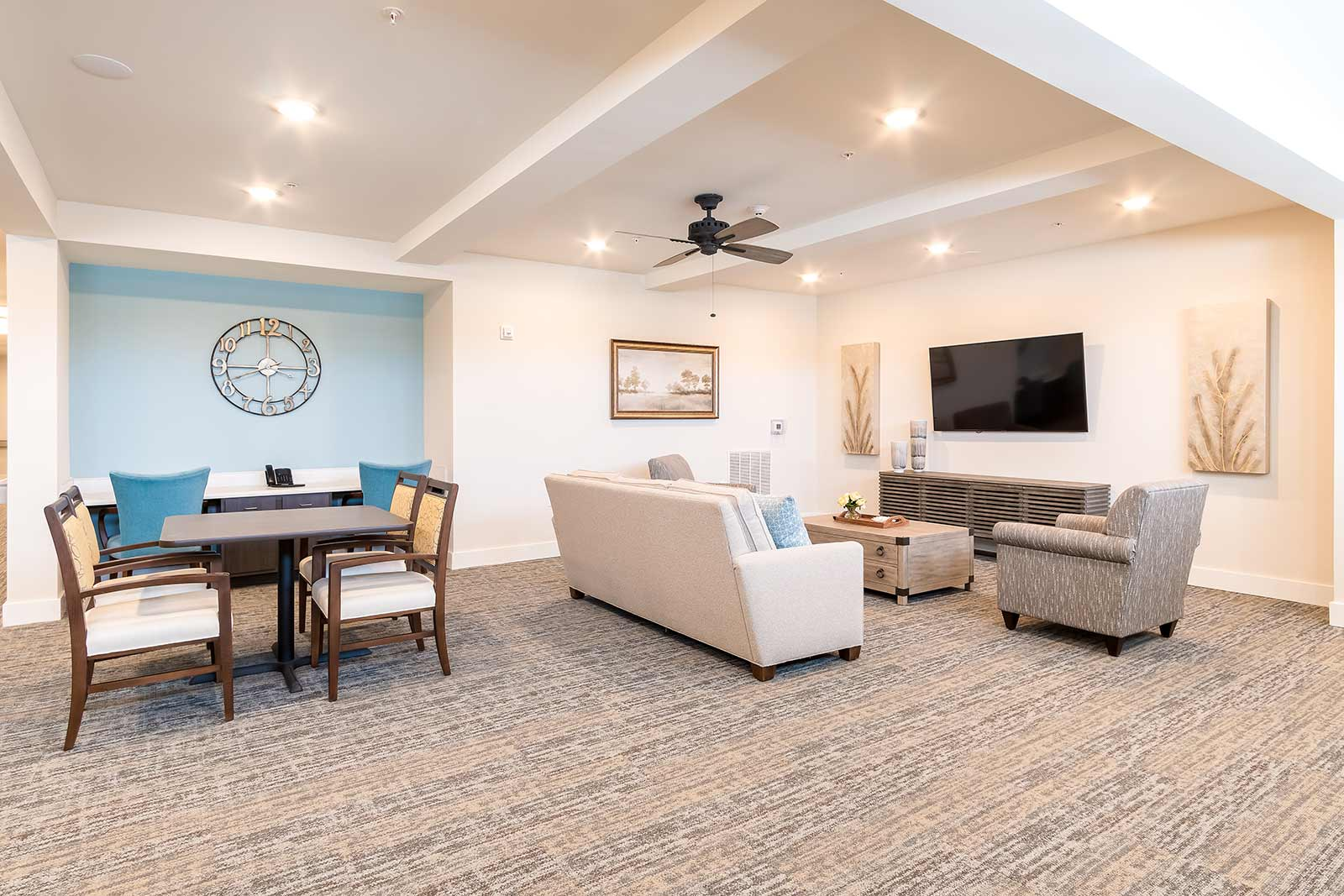 Lounge area with TV, couches, table and chairs in our Plant City FL assisted living and memory care community