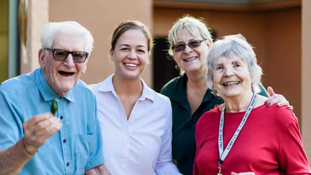 Staff members with senior man and woman in memory care community